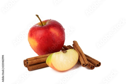 Red ripe apple and aromatic cinnamon sticks on white background