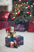 Christmas Eve Concept Teddy Bear In Santa Hat On Gift Box Near Fir Tree With Toys