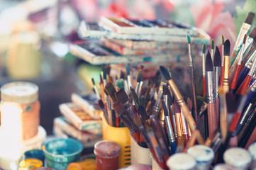 Paint brushes and watercolor paints on the table in a workshop, selective focus, close up.
