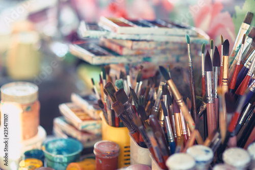 Foto  Paint brushes and watercolor paints on the table in a workshop, selective focus, close up