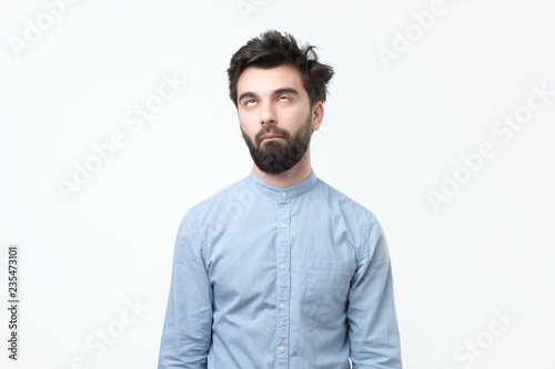 Fotografie, Obraz  Weary hispanic man in blue shirt rolling his eyes up