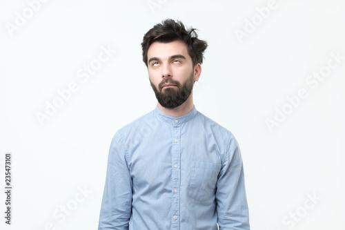 Fotomural Weary hispanic man in blue shirt rolling his eyes up