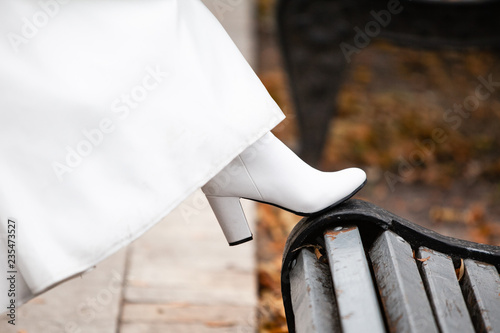 Valokuva  White leather boots with heels under the white dress of the bride