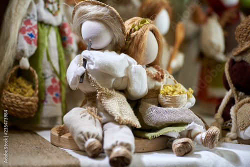 Photo  Ukrainian traditional doll amulet in national bright costume, shepherd with a pi