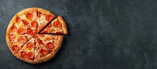 Smakowita pepperoni pizza i kulinarni składników pomidorów basil na czerni betonowym tle. Widok z góry gorącej pizzy pepperoni. Z miejsca na kopię tekstu. Leżał płasko. Transparent