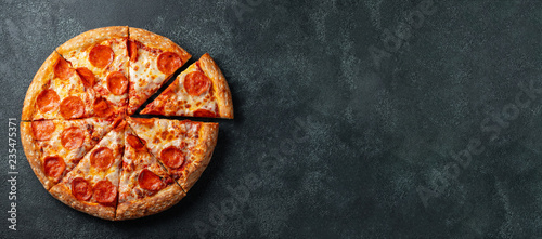 Photo sur Aluminium Pizzeria Tasty pepperoni pizza and cooking ingredients tomatoes basil on black concrete background. Top view of hot pepperoni pizza. With copy space for text. Flat lay. Banner