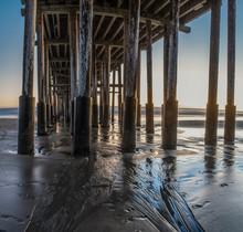 Last Light Fading Behind The Ocean Horizon As Reflecting Wet Sand Illuminates Underneath Wooden Pier At Sunset.
