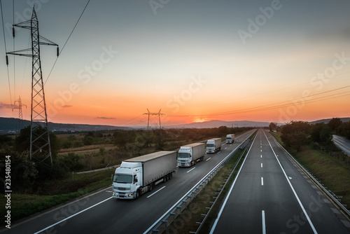 Photo  Four White Lorry Trucks Convoy on highway at beautiful sunset