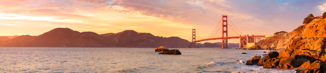 Panoramic view of famous Golden Gate Bridge seen from Baker Beach in beautiful golden evening light. San Francisco, California, USA