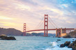 Classic panoramic view of famous Golden Gate Bridge seen from Baker Beach in beautiful golden evening light. San Francisco, California, USA