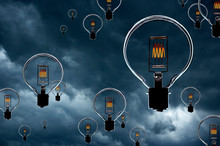 ELECTRIC LIGHT BULBS WITH GLOWING FILAMENTS FLOATING IN SKY WITH STORM CLOUDS