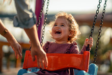 Adorable Little Girl Having Fun On A Swing