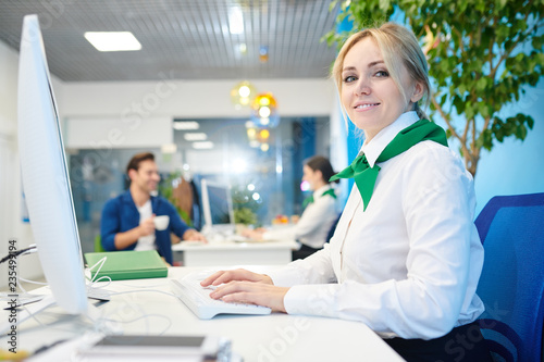 Fototapeta Smiling beautiful young lady wearing white blouse and neck scarf sitting at table and tying on computer keyboard while working in bank and filling online customers card. obraz