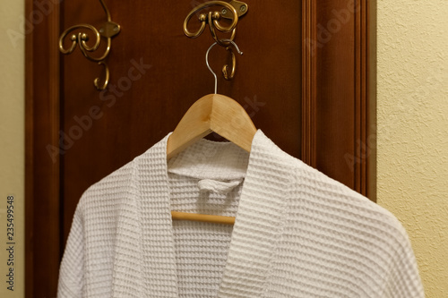 Fotografie, Obraz  White textile robe is hanging on the hook in the bedroom