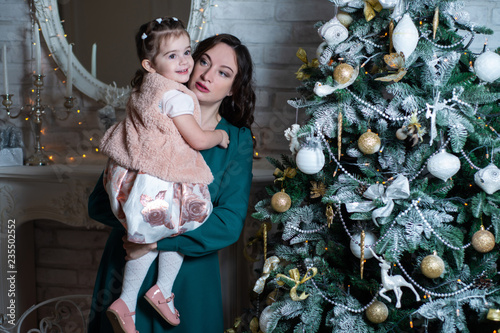 Tuinposter Imagination Merry Christmas and happy holidays. Mother and daughter near the Christmas tree with gifts