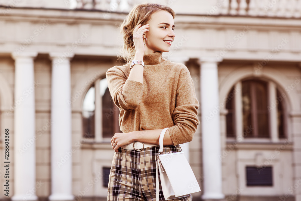 Fototapeta Outdoor fashion portrait of young happy smiling lady wearing trendy beige turtleneck, high-waisted checkered trousers, wrist watch, belt, carrying small white bag, posing in street. Copy, empty space