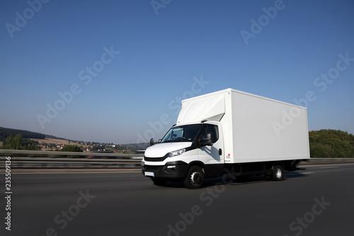 Dynamische Fahrt von einem Transportfahrzeug mit Dorf im Hintergrund