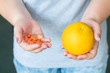 pill supplemens vs natural vitamins choice. drugs and citrus in woman hands.