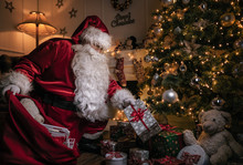 Santa Claus Putting Gifts Unde...