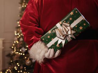 Obraz na PlexiSanta Claus holding christmas gift behind his back