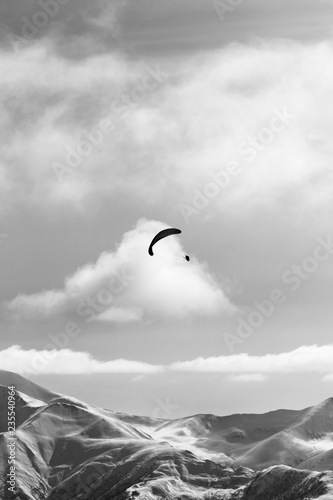 Silhouette of paraglider in winter snowy mountains at nice sun evening