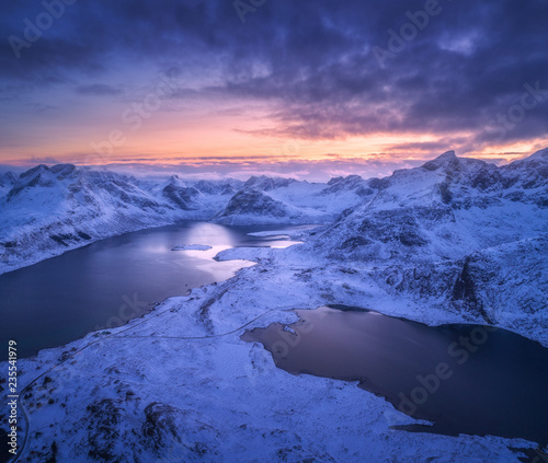 Colline Aerial view of snowy mountains, sea, colorful cloudy sky at night in Lofoten islands, Norway. Winter landscape with snow covered rocks and seacoast and sunset sky. Top view of Norwegian Fjords at dusk