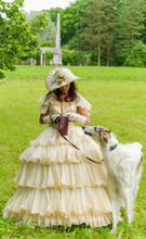 Beautiful, Young Girl In A White Medieval Dress With A Big White Hat On Her Head, Walking With A Hunting, Hound Dog In A Green Park In The Summer. Historical Outfits.