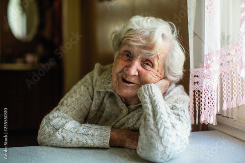 Portrait of elderly pensioner lady sitting at the table.