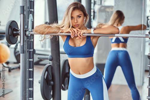 Tela Sexy girl wearing sportswear is posing next smith machine in the fitness center