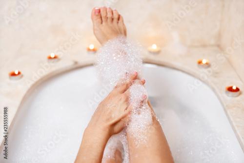 Fotografía  Woman legs in bath foam. Relaxation in spa.
