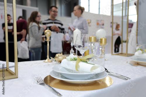Obraz Talerze, sztućce, zastawa stołowa i ludzie w tle - fototapety do salonu