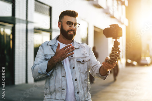 Fotografia, Obraz  Bearded male hipster blogger in trendy glasses standing on city street, holds camera on tripod and shoots video blog
