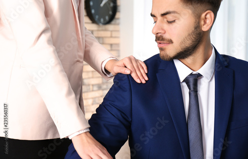 Woman molesting her male colleague in office, closeup Canvas Print