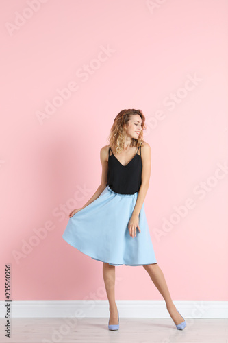 Young woman with beautiful long legs in stylish outfit near color wall. Space for text
