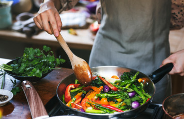 Woman cooking stir fried vegetables
