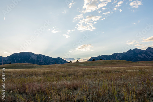 Fotobehang Blauwe hemel grass field with mountains and clouds