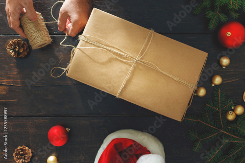 Fotografía Man wrapping christmas present table Rustic background Wrapping top view