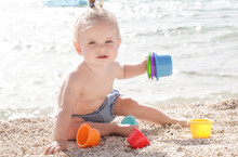 Cute Baby Playing With Plastic Toys On The Pebble Beach Near The Sea