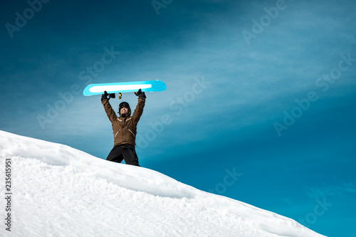 Happy man with snowboard in the mountains
