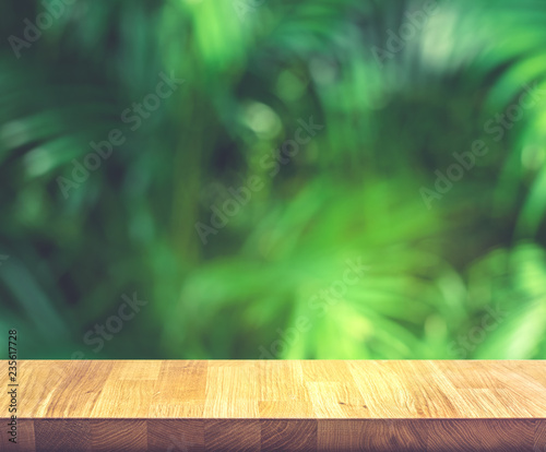 Empty of wood table top on beautiful tropical leaf from garden backgrounds