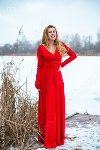 Fotografiet Inspiration at winter, woman in long evening dress on a snow, christmas and magical time
