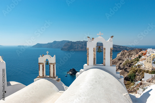 View of Oia town with traditional and famous houses and churches with blue domes over the Caldera on Santorini island. Greece.