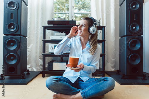 Woman listening to music from a Hi-Fi stereo at home Wallpaper Mural