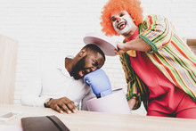 Young Man In Clown Costume On Meeting In Office.