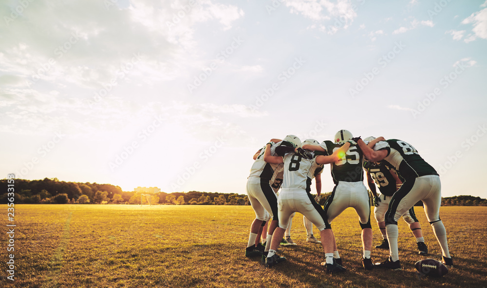 Fototapeta American football players in a huddle during practice