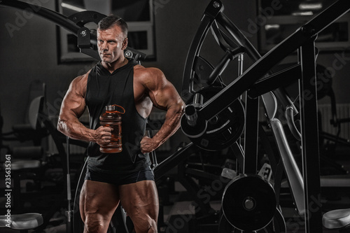Muscular caucasian man on diet resting after exercise And drinking protein powde Fototapeta