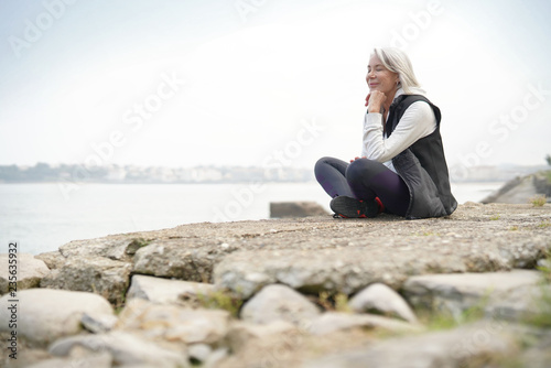 Beautiful elderly woman sitting by the ocean in sportswear