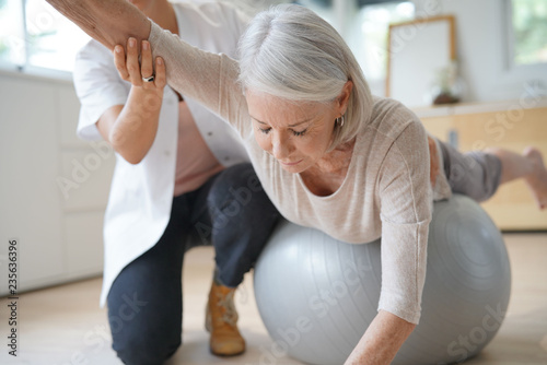 Fotografia  Senior woman exercising with her physiotherapist and swiss ball