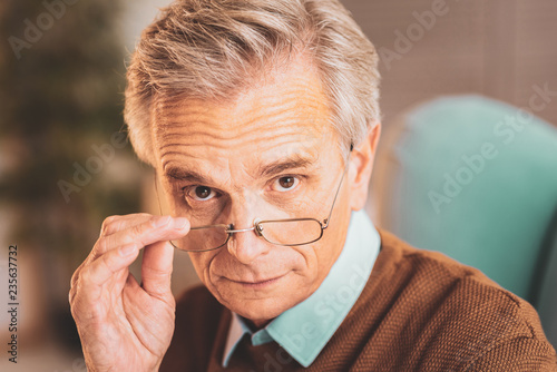 Considerate aged man wearing glasses Wallpaper Mural