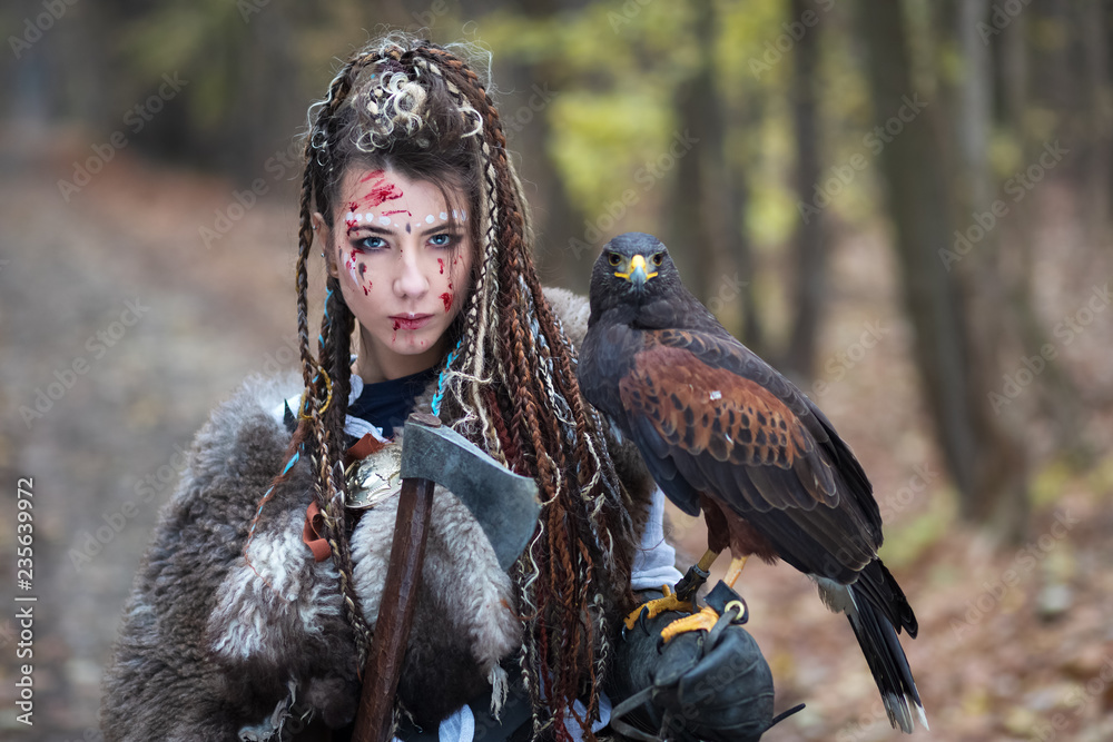 Fototapeta Beautiful Viking warrior woman in woods wearing fur collar, braided hair and specific makeup with face covered in blood holding hawk in hand. Northern woman with her predator in forest
